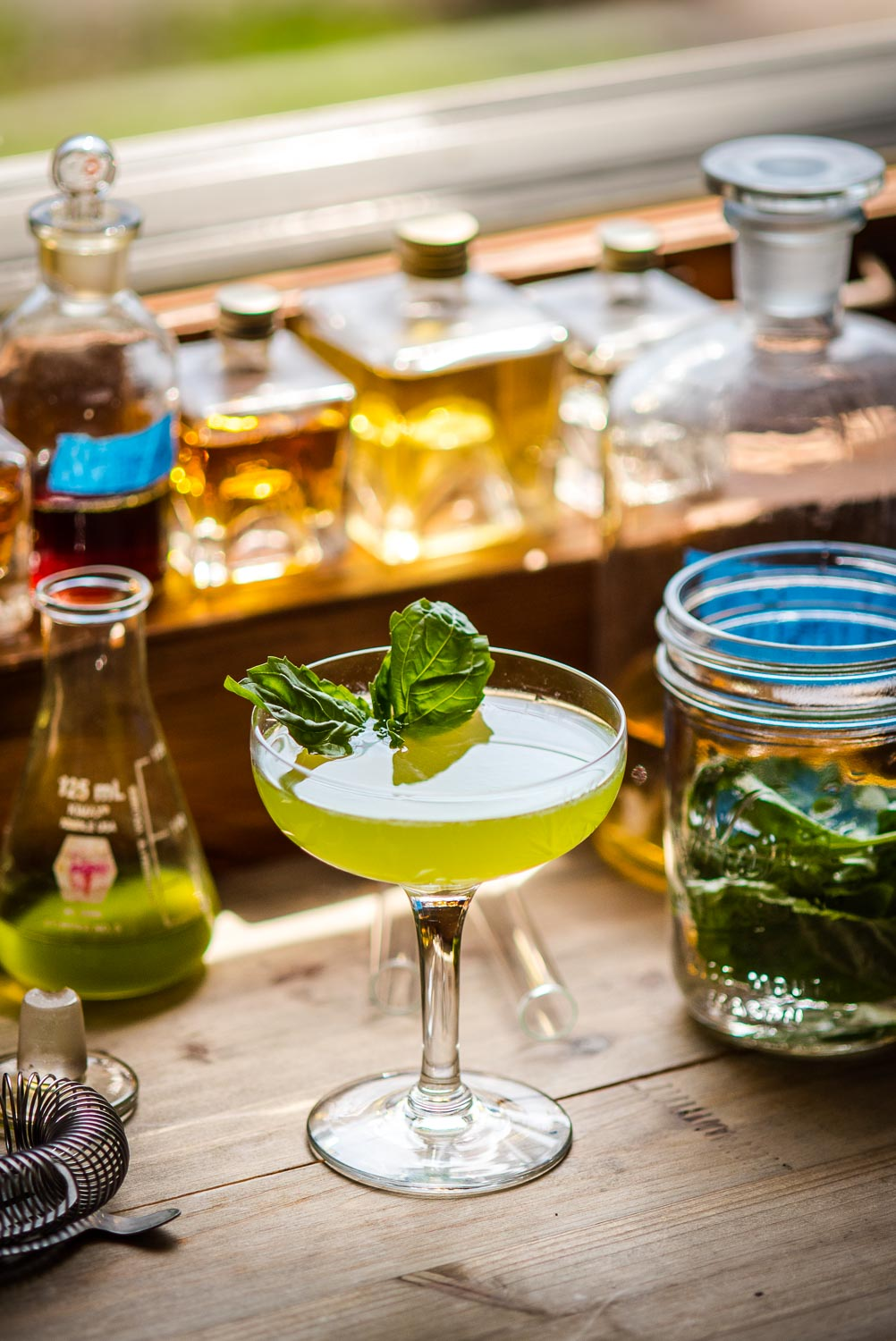 green craft cocktail on a kitchen table