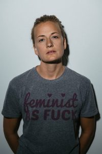 portrait of a feminist woman leaning against white wall in Madison WI studio